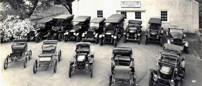 An old, black & white photo of Stanley cars in front of the Marshall Steam Museum building