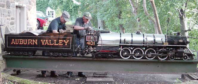 """Two gentlemen in engineer caps working on the 4-8-4 Northern Engines #401, the side of the train reads in all caps """"Auburn Valley"""""""
