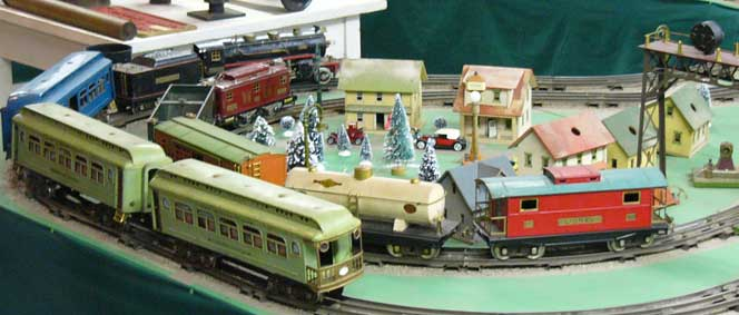 Several toy trains on a circular portion of a track
