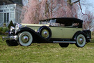 The 1932 Packard Phaeton Model 905 sits in front of a blooming cherry tree. The car is a light green/yellow with Black highlights, features white wheels, and has an extra wheel attached to the side of the car.