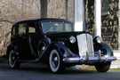 The 1937 Packard Model 1508 sits in front of a white arch. It is a fully black car.