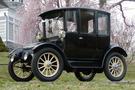 The 1916 Rauch & Lang Electric Brougham, it's an all black car with white wheel spokes in front of a blooming cherry tree