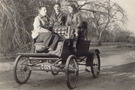 A black and white photo of three people riding on the 1901 Stanley Mobile, Lex, Irene & Barbra DuPont, two men and a woman