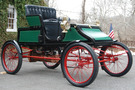 The 1905 Stanley Model CX looks similar to a buggy, has an open top, has a green body and red wheel spokes/undercarriage