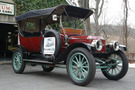 The 1912 Stanley model 87 has a firetruck red body and mint green wheel spokes and under carriage. The rop of the car is up, covering the seats from above while leaving the sides of the car open