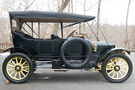 The 1913 Stanley Model 76 has a dark green body and a lemon yellow undercarriage and wheel spokes. The top of the car is up, covering the top of the car but not the sides.