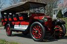 """The 1915 Stanley Mountain Wagon Model 820 has a red body and red wheel spokes. This car, sometimes called a """"steam bus"""" has five rows of seats. There is a sign on the side that says """"Friends of Auburn Heights, Yorklyn, DE"""""""