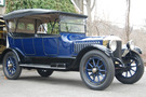 The 1916 Stanley Model 725 has a cobalt blue body and wheel spokes. The top is up, and it covers both the top and sides of the car