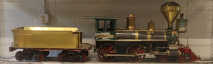 This American Locomotive was made in the 1960's by Tom Marshall. THe train is green and gold, and the wheels are red