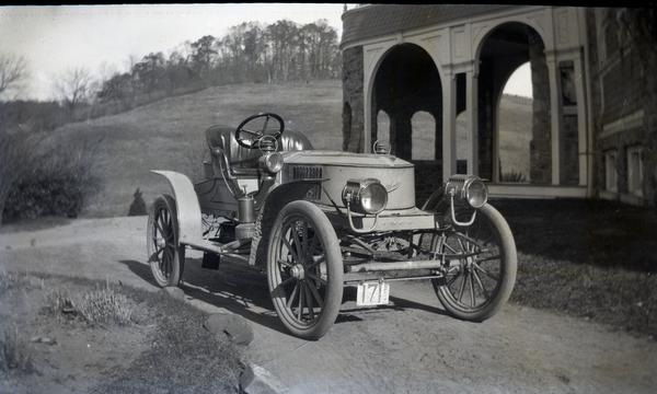 The 1907 Stanley Model K Semi-Racer sits in front of the arch of the Auburn Heights mansion. The photograph is in black and white