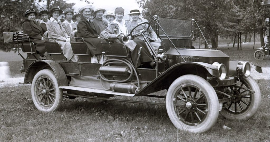 A group of women are seated in the Mountain Wagon in this black and white photo