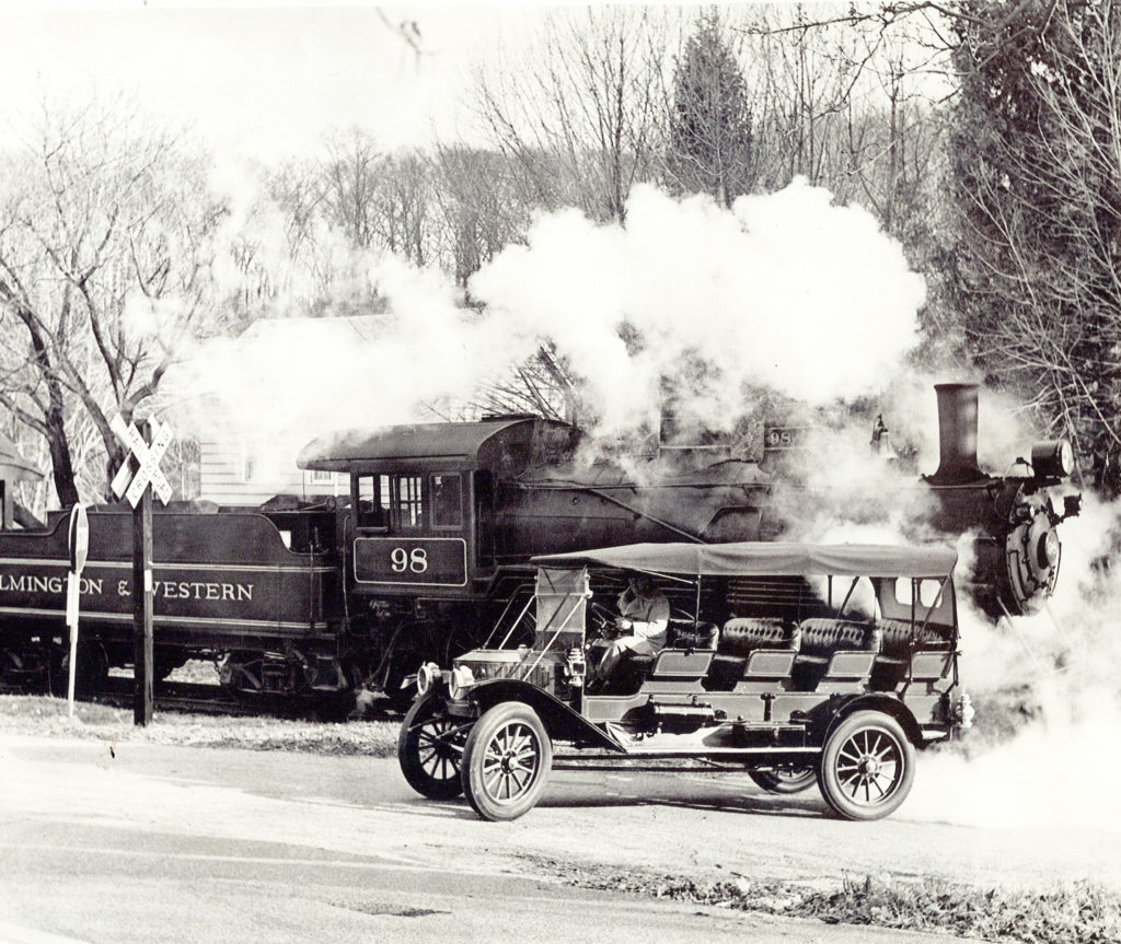 """The Mountain Wagon drives in front of a large steam train with the words """"Wilmington & Western"""" emblazoned on the side"""