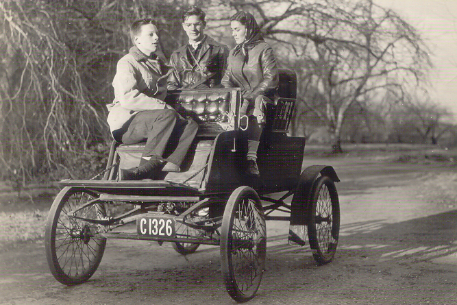 A black & white photo of three people sitting in the 1901 Stanley Mobile, which looks more like a carriage than a car