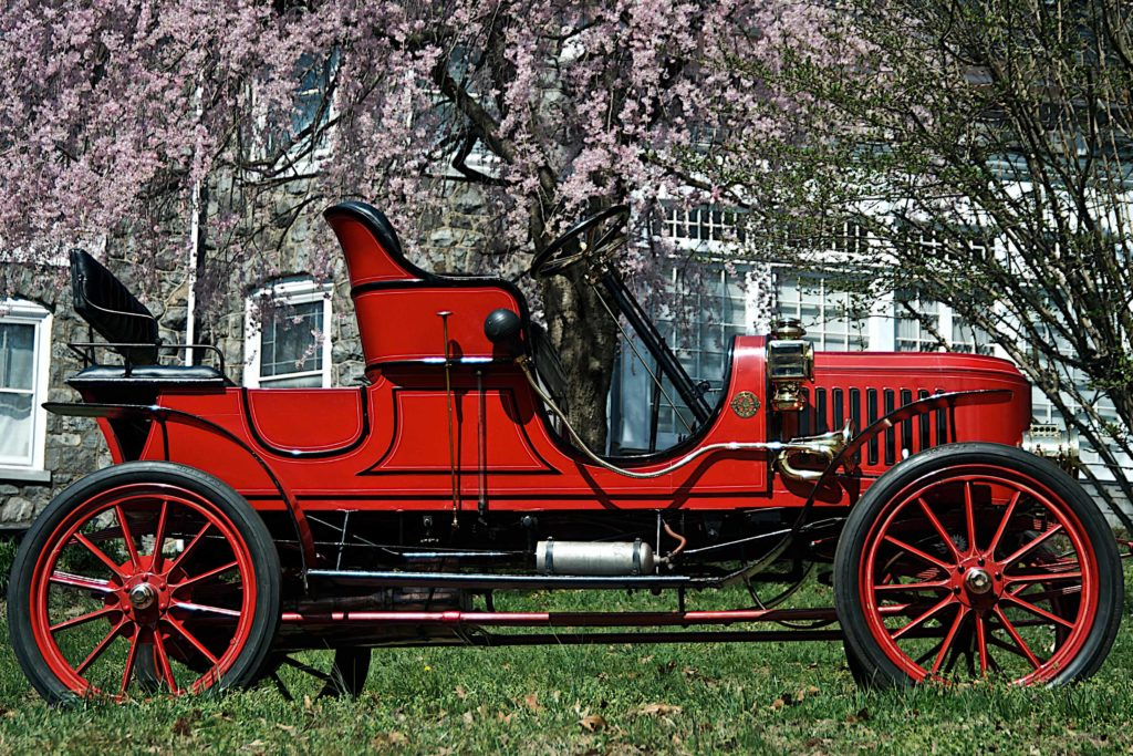 The 1908 Stanley Model EX is a fully red car that has black accents, it looks like a mix between a car and a carriage