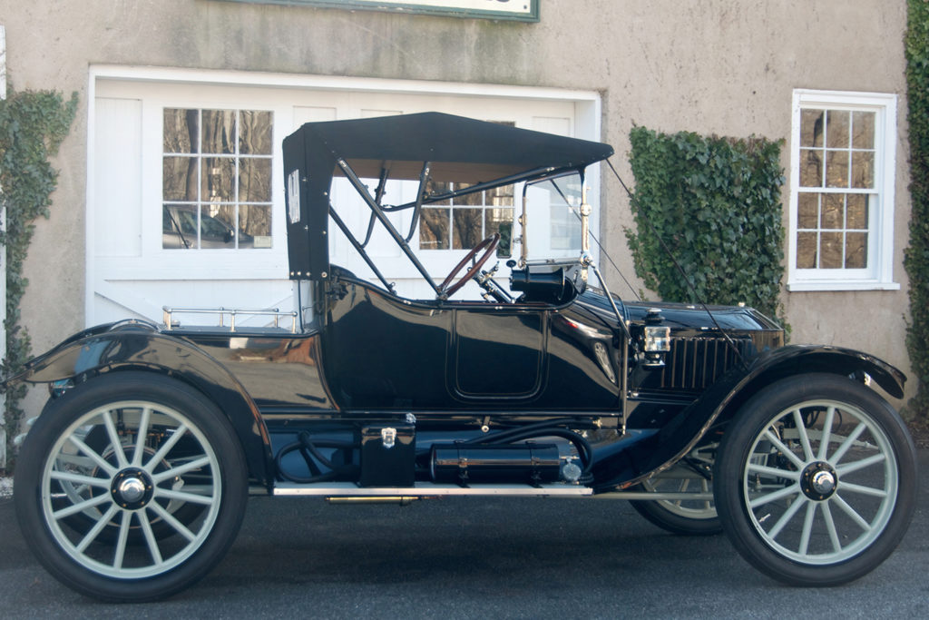 The 1913 Stanley Roadster Model 78 is a glossy back car, with blue wheels, a space on the back for trunks, and a black top