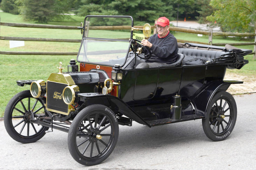 The 1914 Ford Model T is a mostly black car with a red front. An older gentleman in a red ballcap sits behind the wheel