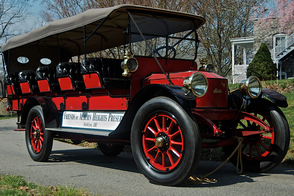 """The 1915 Stanley Model 820 Mountain Wagon has five rows of seats, fitting across approximately three people per row. The car is all red with a black top. There is a sign on the side that reads """"Friends of Auburn Heights Preserve, Yorklyn, DE"""""""