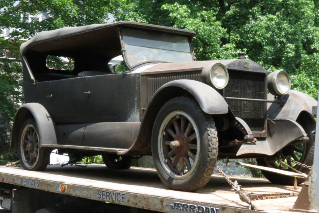 The 1924 Stanley Model 750 is very rusty, and there is little to no paint on the entire car, there are chains attached to the bottom of the car, as it is being hauled