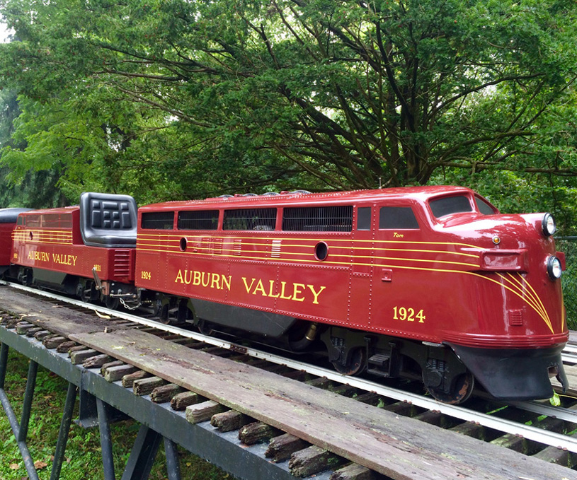 """The F-7 Double Unit is a mostly red train with the words """"Auburn Valley"""" painted on the side in yellow"""