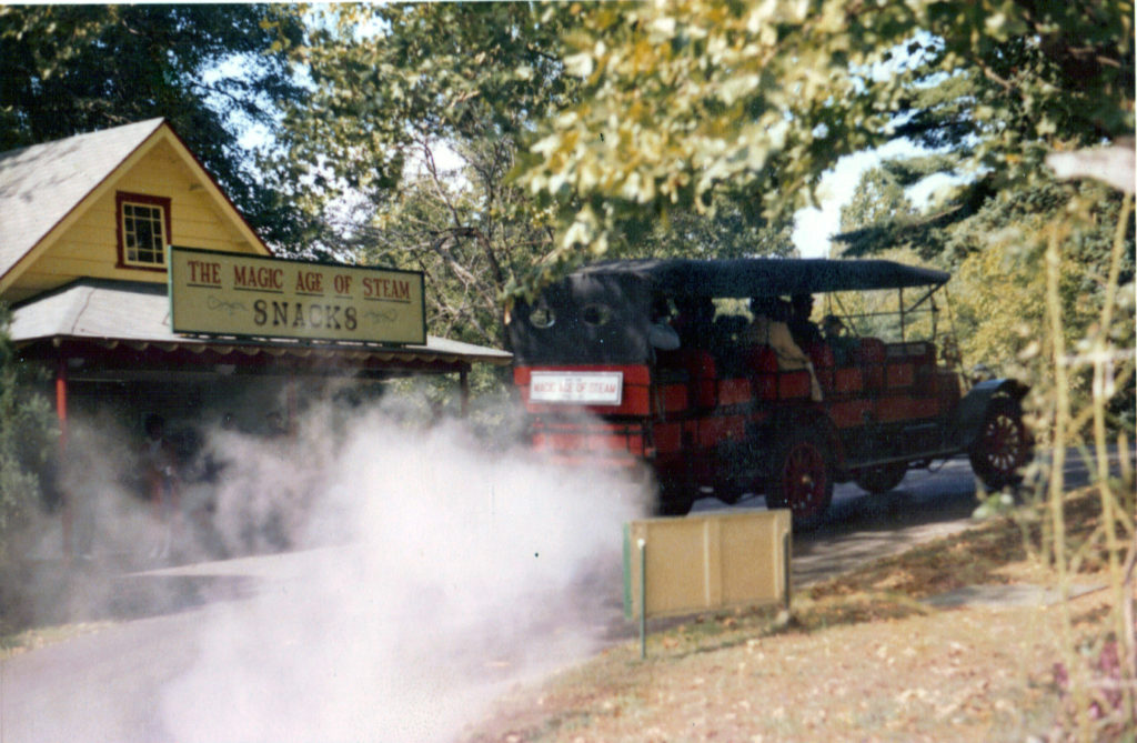 """The back of the Mountain Wagon is shown passing in front of a sign that reads """"The Magic Age of Steam, Snacks"""""""