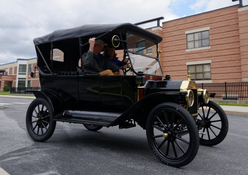 A man and a woman are riding in the Model T, in front of a brick building in a parking lot