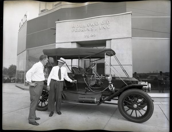 James F. Hollywood and T. Clarence Marshall stand in front of a 1910 Stanley Model 71 at Hollywood-Perkins Desota & Plymouth Dealership, the photo is fully black and white