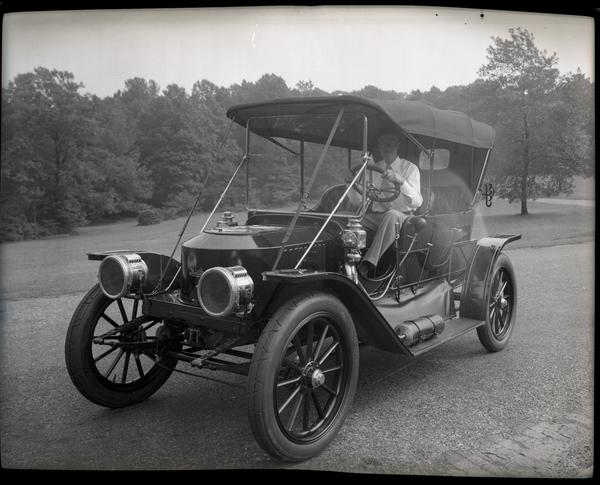 """Tom Marshall is in the driver seat of a Stanley Model 71. The front of the car is """"coffin shaped"""""""