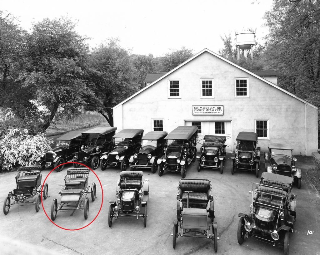 In this black and white photo several antique cars are parked in front of the Marshall Steam Museum