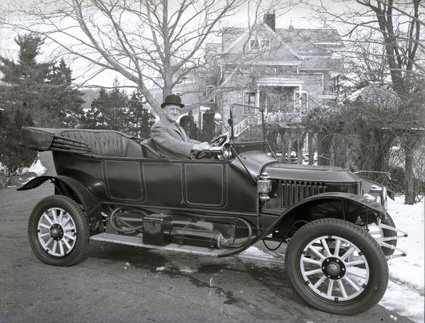 A black and white photo of the Stanley Model 76, with T. Clarence Marshall, an old white man, behind the wheel