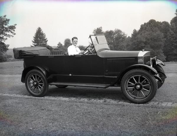 In this black and white photo, Tom Marshall, at this point a young man, sits in a Model 735 in a field